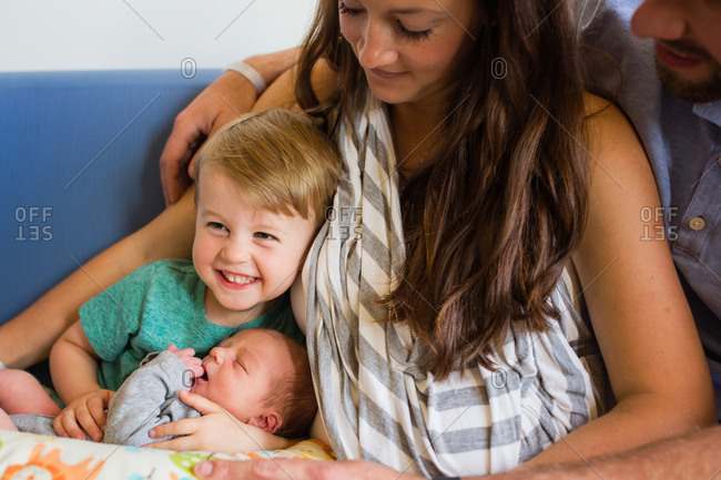 Happy family sitting on blue sofa with newborn baby