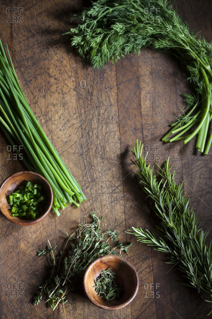 Green herbs on wooden cutting board