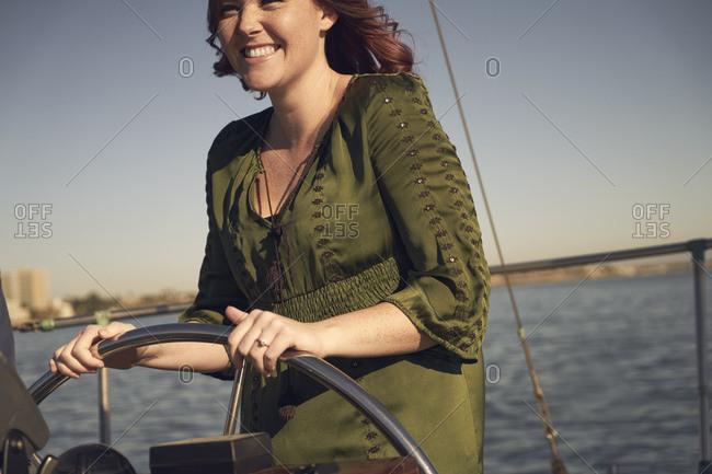 Happy woman steering sailboat on ocean