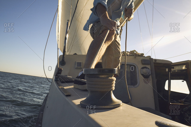 Low section of man pulling rigging on sailboat