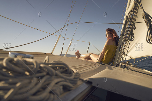 Side view of thoughtful woman sitting on deck of sailboat