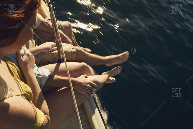 Couple sitting on deck of sailboat with legs dangling over water