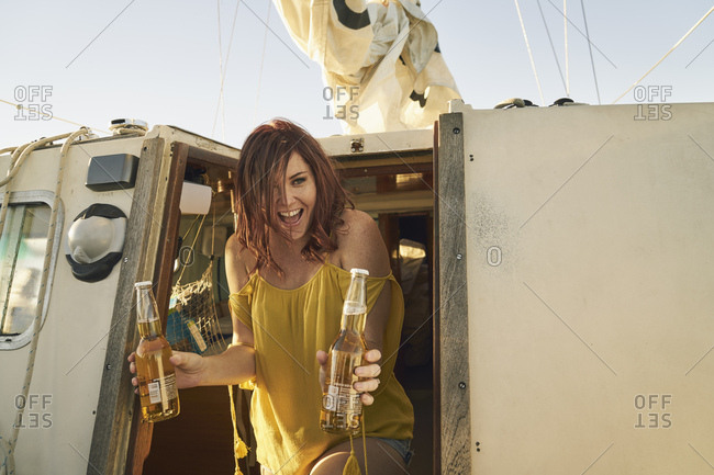 Cheerful woman holding beer bottles on sailboat