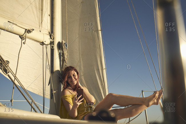 Happy woman taking selfie through smart phone while sitting on sailboat