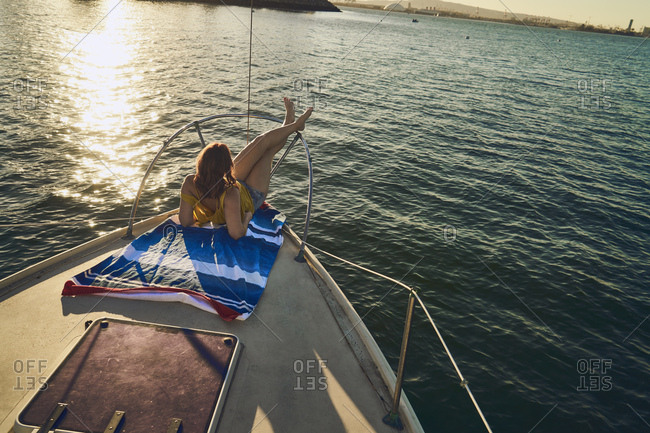 High angle view of relaxed woman sitting on sailboat desk at sunset