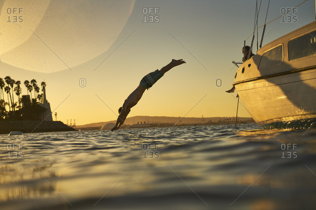 Man diving into ocean from sailboat at sunset