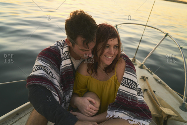 High angle view of romantic couple wrapped in blanket sitting on yacht during sunset