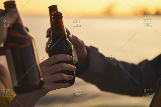 Cropped image of friends toasting beer bottles against sea during sunset