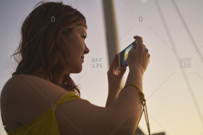 Woman photographing through smart phone from sailboat at sunset