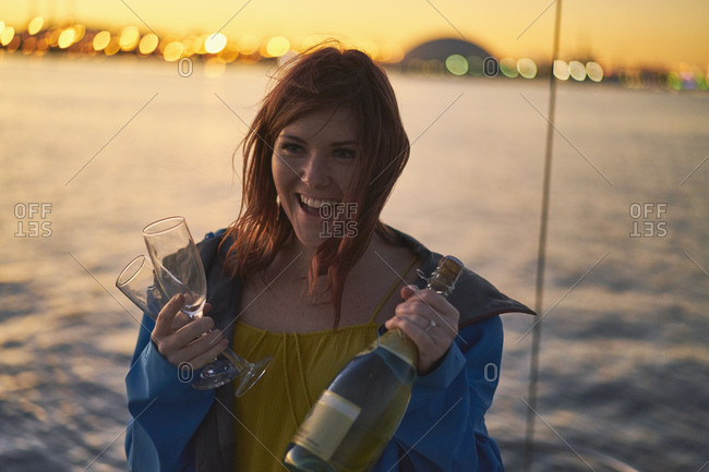 Cheerful woman holding champagne bottle and flutes against sea during dusk