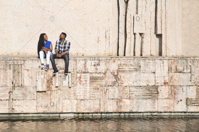 Talking young couple sitting on a wall near water