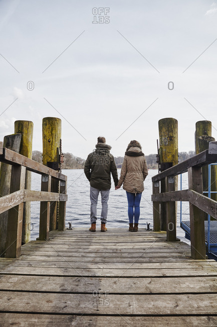 Germany- Potsdam- rear view of young couple standing on jetty at Havel River