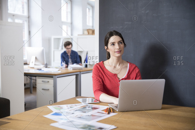 Woman using laptop on table in office thinking