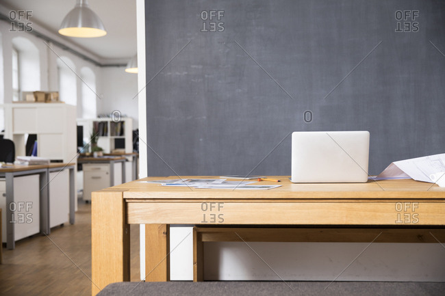 Laptop on desk in empty office