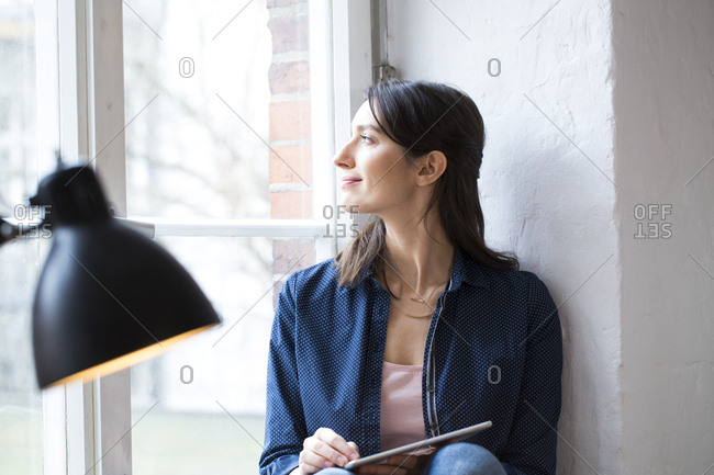 Woman with tablet looking out of window in office