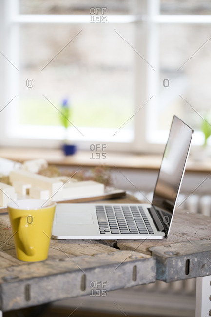 Laptop and coffee cup in modern informal office