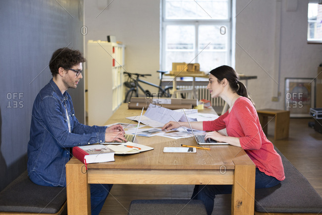 Man and woman working on project in office together