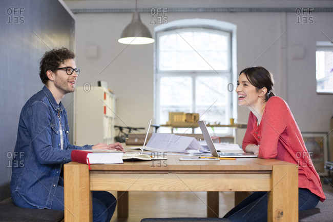 Happy man and woman working on project in office together