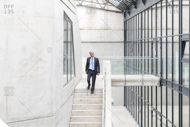 Mature businessman walking down stairs