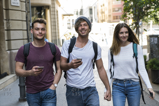 Friends with cell phones walking in the city
