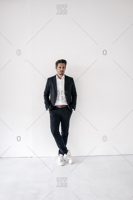 Portrait of confident businessman standing with hands in pockets