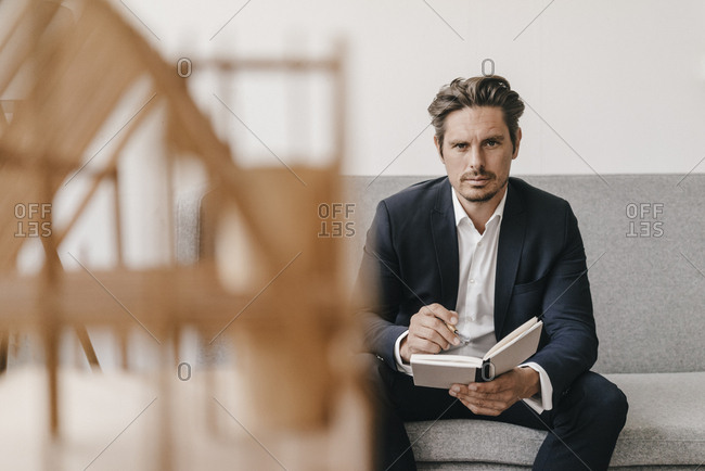 Man with notebook on couch with architectural model in foreground