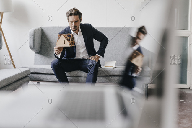 Architect on couch examining architectural model