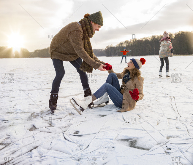 Man helping ice skating woman up on icy surface of frozen lake