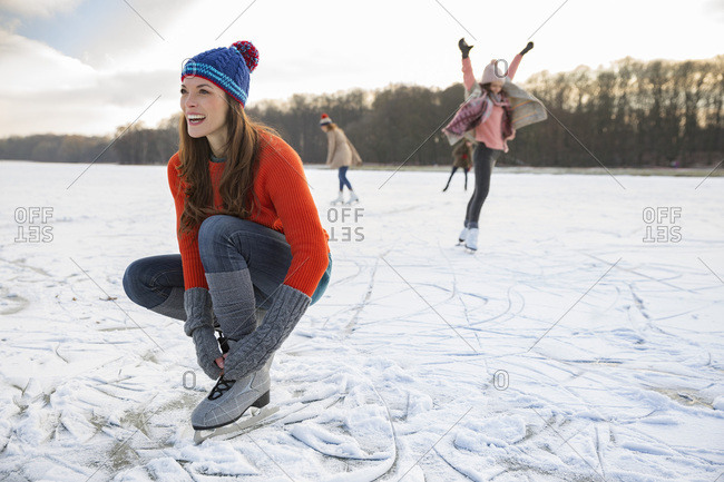 Woman tying her ice skates on frozen lake