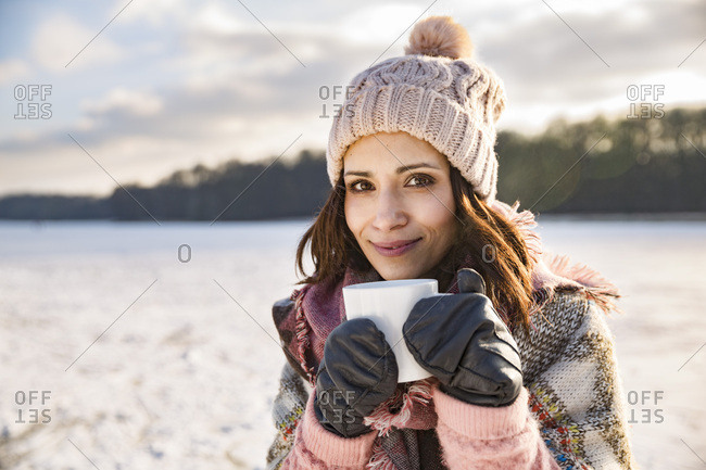 Portrait of smiling woman drinking hot beverage from a cup outdoors in winter