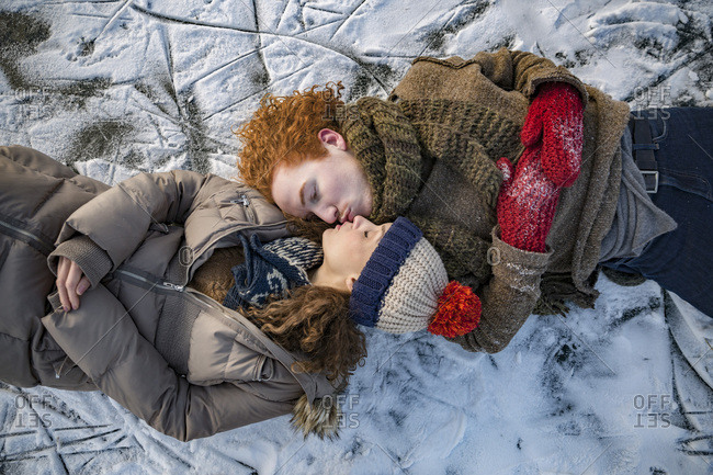 Couple lying down on frozen lake surface kissing