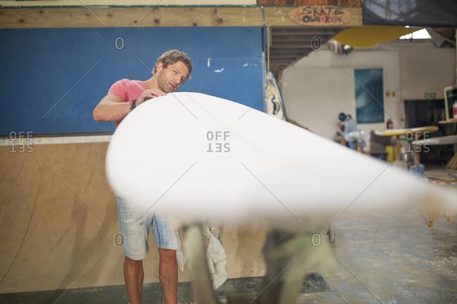 Surfboard shaper workshop- man checking surfboard
