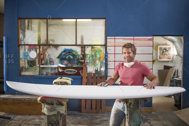 Surfboard shaper workshop- portrait of smiling surfshop employee with surfboard