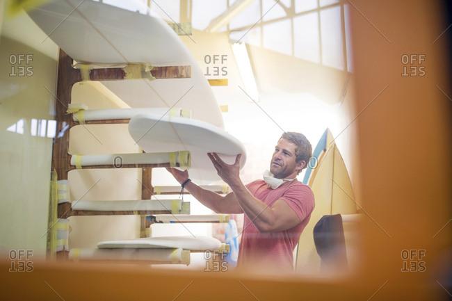 Surfboard shaper workshop- man stacking surfboards