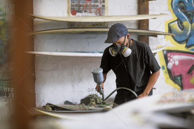 Surfboard shaper workshop- surfboard shop employee spraying surfboard