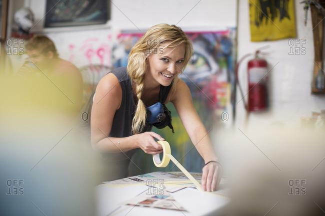 Surfboard shaper workshop- smiling female employee working on surfboard