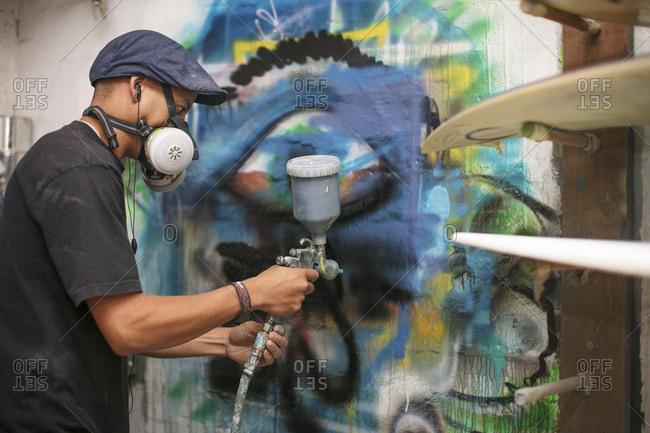 Surfboard shaper workshop- surfshop employee spray painting wall design