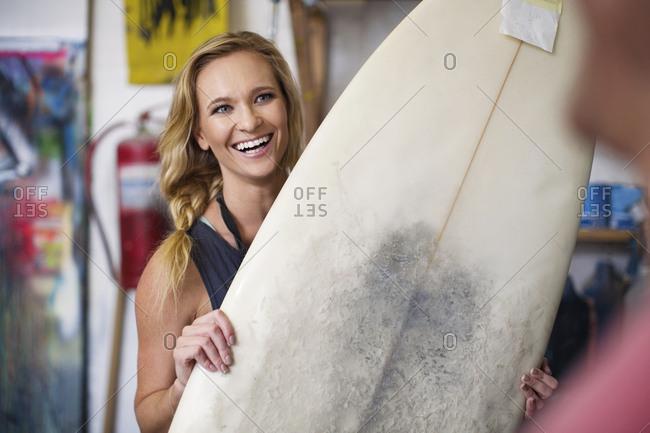 Surfboard shaper workshop- female employee smiling with surfboard