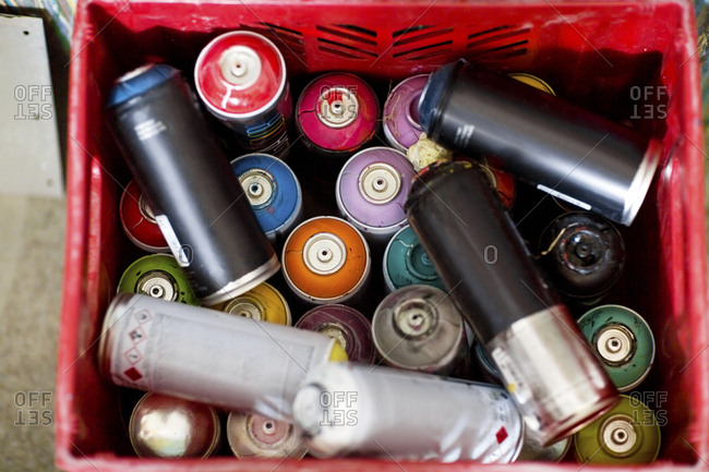 Spray paint cans in plastic crate