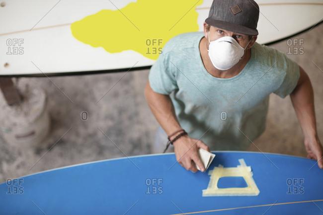 Surfboard shaper workshop- surfshop employee wearing dust mask