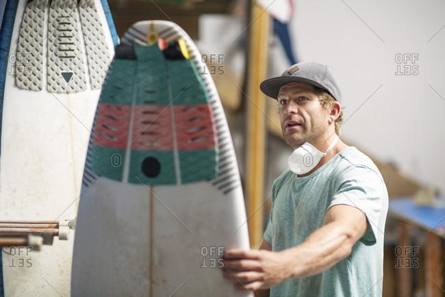 Surfboard shaper workshop- surfshop employee admiring surfboard