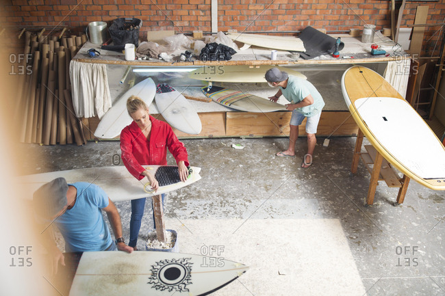 Surfboard shaper workshop- surfshop employee working on surfboards