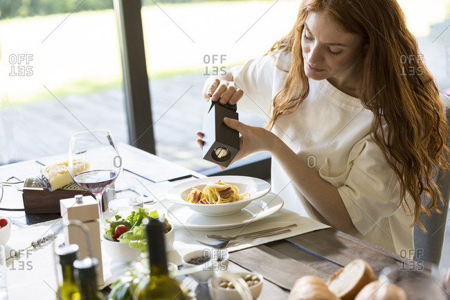 Woman seasoning her spaghetti carbonara