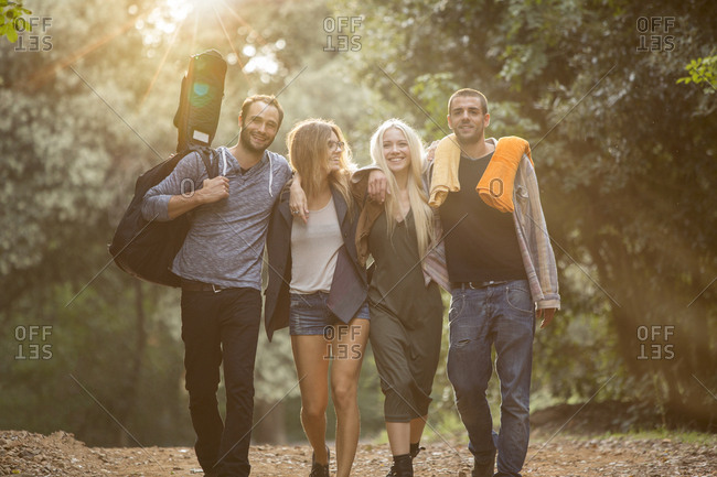 Four happy friends walking on path in the forest