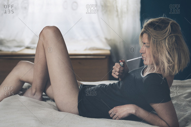 Young woman smoking in bed in her room.