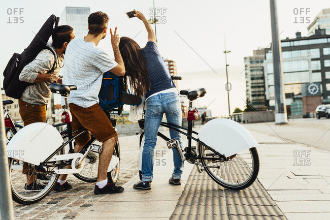 Three people with bicycles photographing self in city