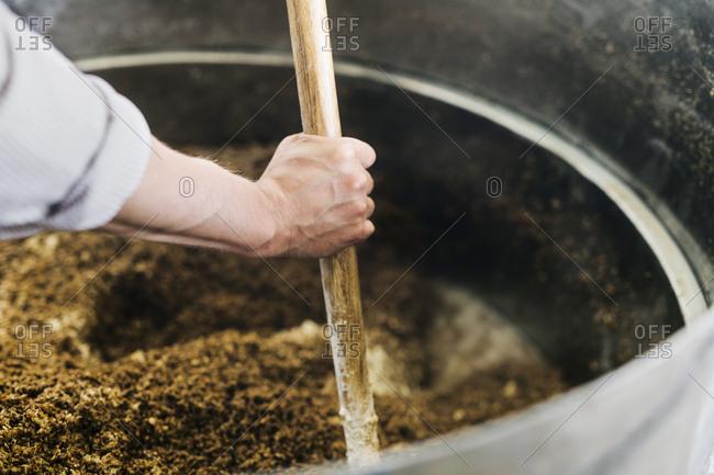 Worker mixing ingredients in vat