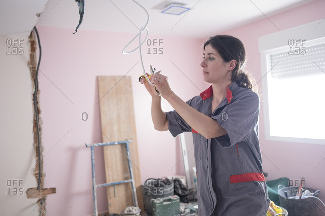 Woman working at home with masonry and renovation. Electrical and telecommunications installation.