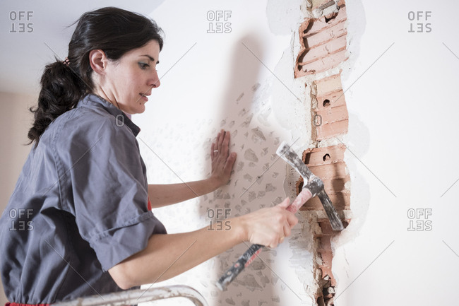 Woman working at home with masonry and renovation. Chopping the wall with a chopper hammer