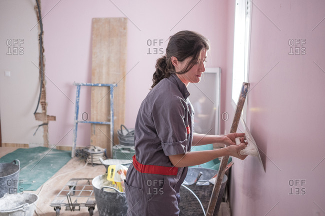 Woman working at home with masonry and renovation. Unfirming the wall paste with the flat tool